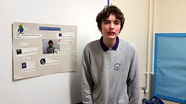 A lad standing next to a poster of how he sees a 'Fairer Scotland' by 2030.